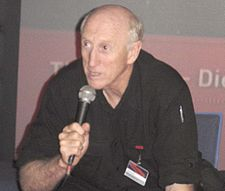 waist-high portrait wearing black shirt, holding microphone, leaning forward and speaking